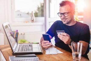 Homme avec ordinateur et carte de crédit