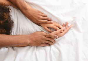 Les mains d'un couple au lit