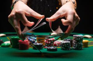 mains mélangent cartes de poker devant des jetons
