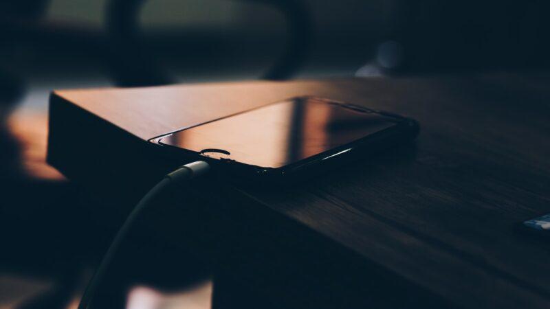 Photographie De Mise Au Point Peu Profonde De i Phone 7 Noir En Charge Sur Une Table En Bois Marron