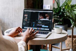 femme utilise macbook gris sur table marbre blanche pour monter vidéo youtube à optimiser